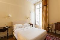 a golden-hued double bedroom in Paris luxury apartment