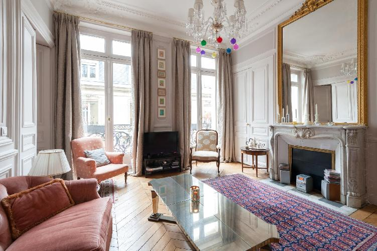 elegant living room with high ceilings, parquet floors, and intricate moldings in Paris luxury apart