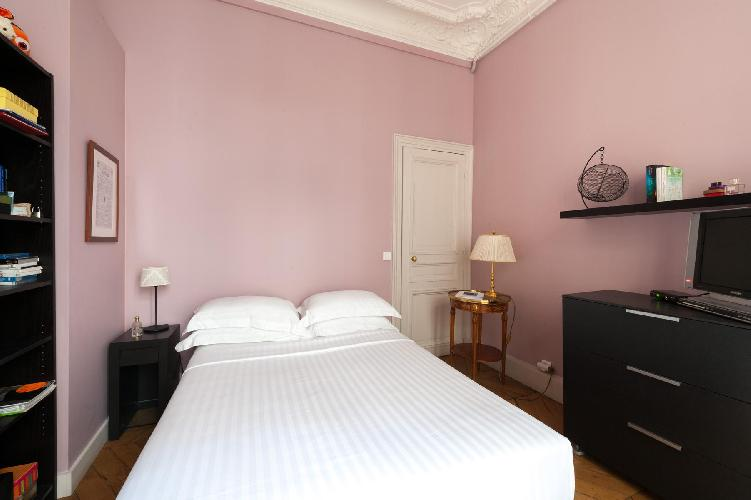 pale pink bedroom with an intricate rug in Paris luxury apartment