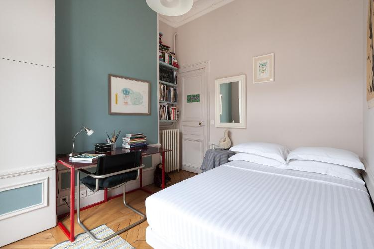 blue-green bedroom with a monochrome canvas and vivid red desk in Paris luxury apartment
