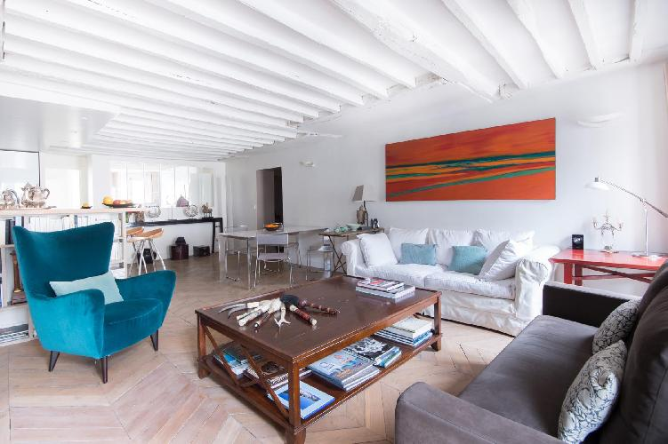 gray and white sofas, bright blue armchair, and dark wooden coffee table in Paris luxury apartment