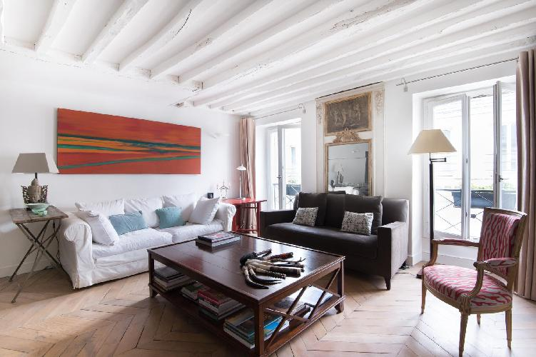 chic living room with original stripped parquet flooring and white-washed wooden beams, a bold blue