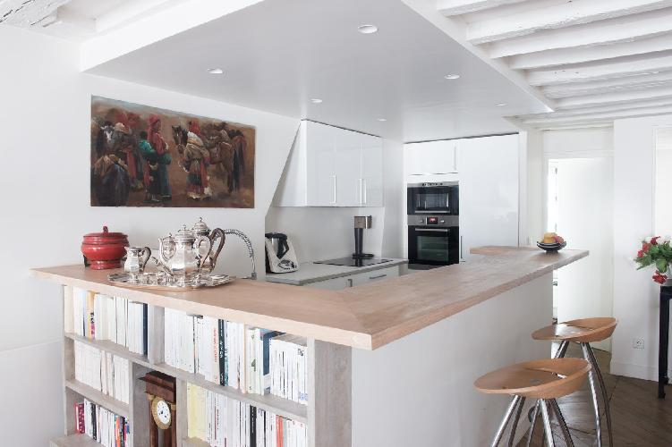 contemporary and well-equipped kitchen with sleek breakfast bar with built-in bookshelves in Paris l