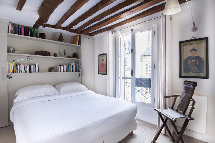 chic master bedroom with mahogany beams run the length of the ceiling over a queen-size bed in Paris