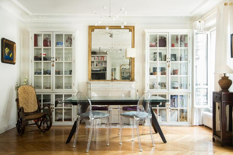 elegant dining area with glass-topped table surrounded by ghost chairs in Paris luxury apartment