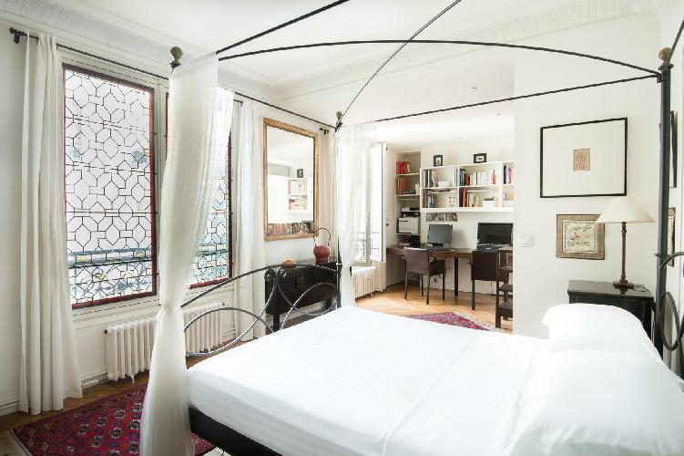 ensuite master bedroom with patterned rugs and delicate artworks surround a gossamer-curtained four-