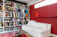 second sitting room with floor-to-ceiling bookshelves and a white sofa in Paris luxury apartment