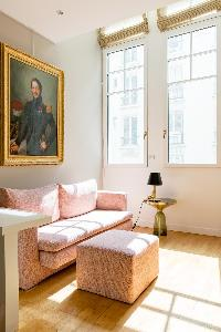 pinkish sofa beneath a  large portrait in gilded frames in Paris luxury apartment