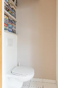 white toilet with bookshelves in Paris luxury apartment