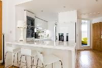 sleek white kitchen with breakfast bar and stools in Paris luxury apartment