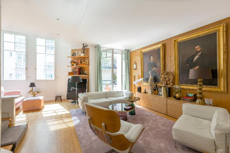 elegant sitting room with a pair of large portraits in gilded frames hang above contemporary furnitu