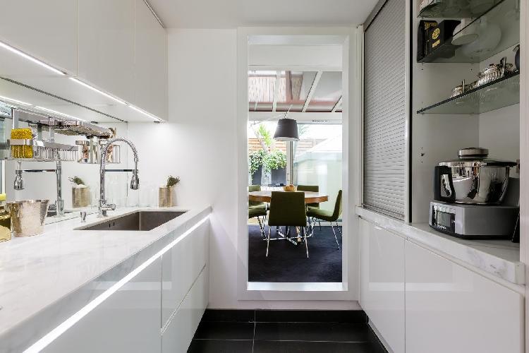 sleek white kitchen and dining area in Paris luxury apartment
