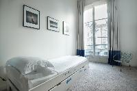 white-walled single trundle bed with cream and turquoise drape in Paris luxury apartment