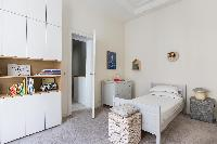white-walled single bed with en suite bath in Paris luxury apartment