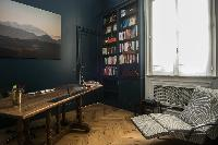moodily decorated study beneath framed artwork, and with reclining chair in Paris luxury apartment