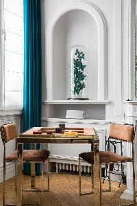 stylish square table and 2 brown chairs with turquoise drape behind in Paris luxury apartment
