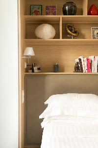 taupe bed frame and shelves at the head board in Paris luxury apartment