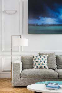 gray sofa beside stylish white floor lamp beneath framed artwork in Paris luxury apartment