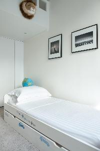 white-walled single trundle bed beneath black-and-white artworks in Paris luxury apartment