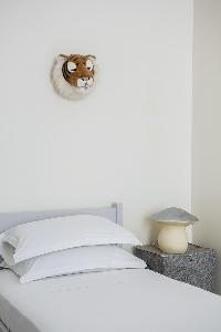 white-walled single bed beneath tiger head artwork in Paris luxury apartment