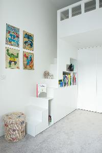 kids loft bedroom with white bookshelves and staircase in Paris luxury apartment