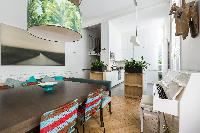 crisp and contemporary dining area with striking square dining table for a centrepiece and white pia