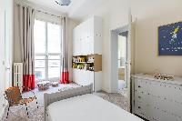 white-walled single bed with cream and scarlet drape in Paris luxury apartment
