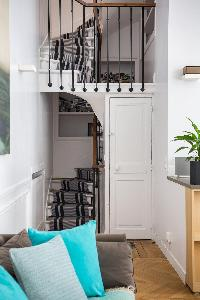 spiral staircase with gray carpet rug in Paris luxury apartment
