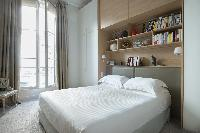 chic bedroom with wooden shelves and gray drape in Paris luxury apartment