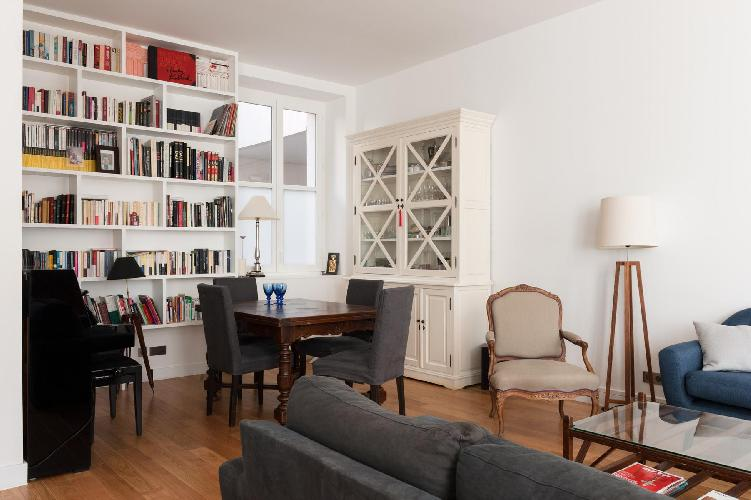 sitting room with 2 dusky sofas, white-draped windows, and a simple wooden dining table for four, we