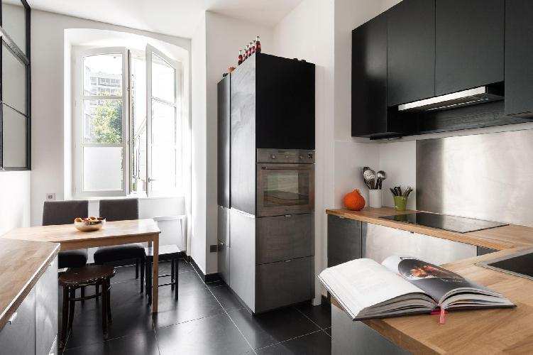 smart kitchen with a striking interior window, and wooden table for 4 in a 4-bedroom Paris luxury ap