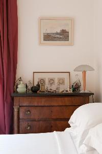 taupe-painted bedroom with antique bedside tables, framed artwork, and plum drape in Paris luxury ap