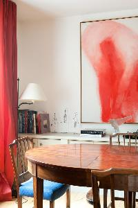 glossy wooden dining table, blue chairs, framed abstract artwork and red drape in Paris luxury apart
