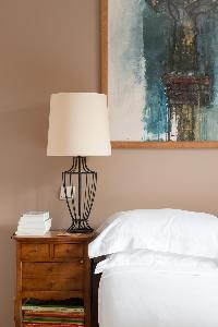 taupe-walled master bedroom with honeyed wood bedside table in Paris luxury apartment