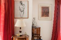 honeyed wood furnitures and framed artworks between red drapes in Paris luxury apartment