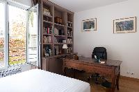 taupe-painted master bedroom with antique desk and bookshelves lined with diverse volumes in Paris l