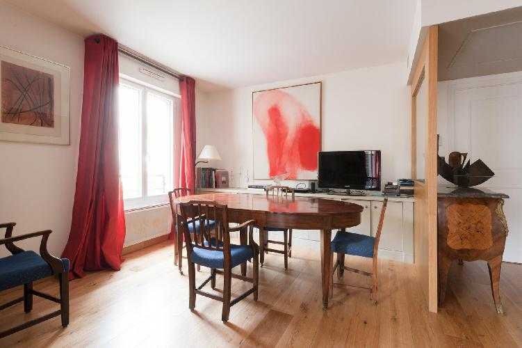 glossy wooden dining table, blue chairs, and red drape in Paris luxury apartment