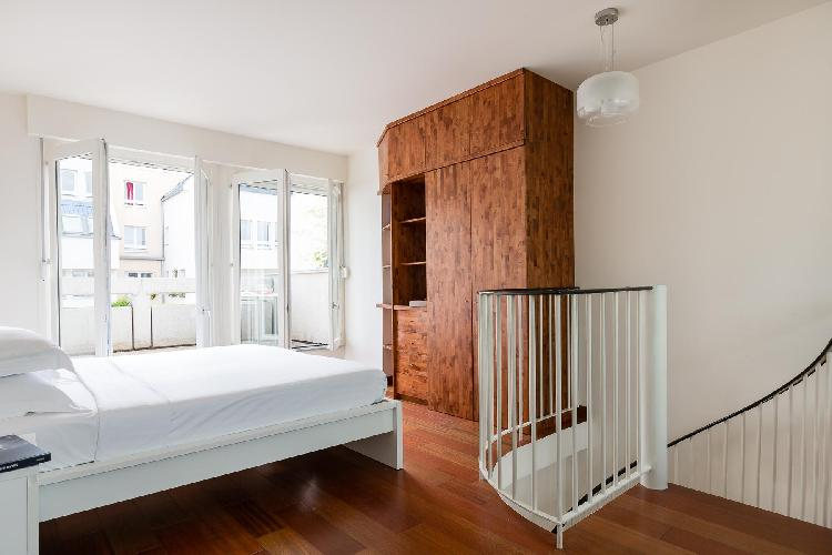 spiral staircase leads to the second bedroom with windows leads to a balcony in Paris luxury apartme