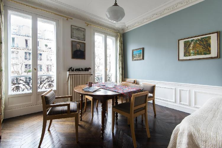 cozy dining room with pale-blue walls lined with paintings and a wooden table in Paris luxury apartm