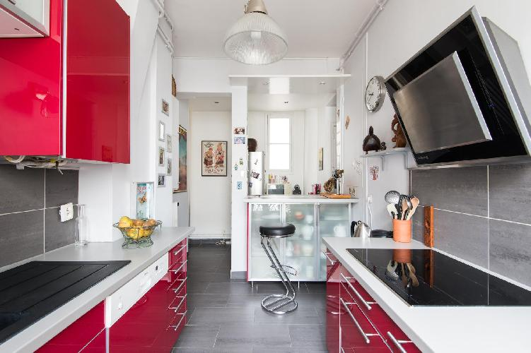sleek kitchen decorated in red and white with a slick breakfast bar in Paris luxury apartment