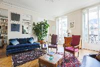 cozy  sitting room with colourful sofas and armchairs, oriental rugs and lots of striking artworks i