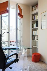 books lined wall, glass study table and Juliet bacony in Paris luxury apartment