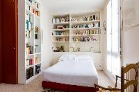 books lined wall and double bed in Paris luxury apartment