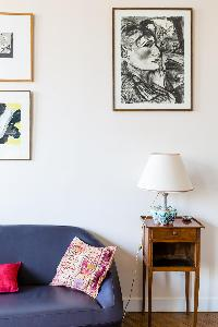 gray sofa and wooden nightstand with lamp on top beneath framed artworks in Paris luxury apartment