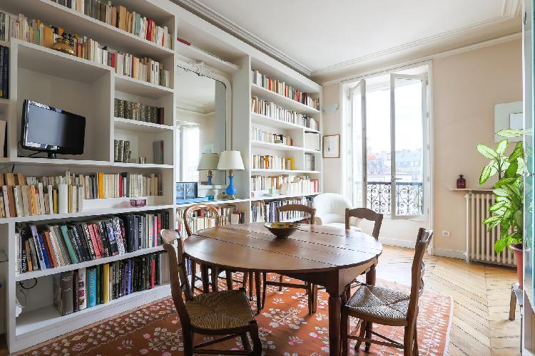 open-plan dining area with books lined wall surrounded by a round antique table for five in Paris lu