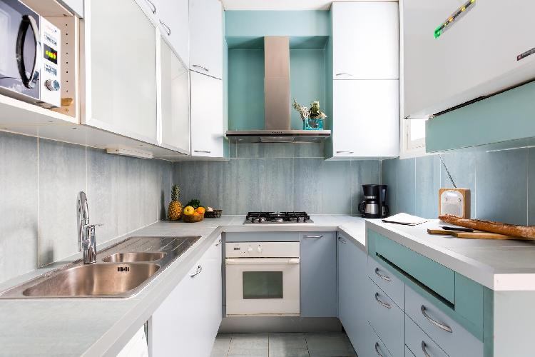 well-equipped kitchen smartly decorated in white, grey and blue in Paris luxury apartment
