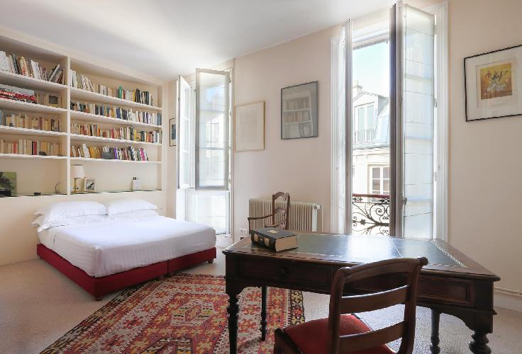 en suite master bedroom in red-and-cream hues with a double bed, an antique desk, books and artworks