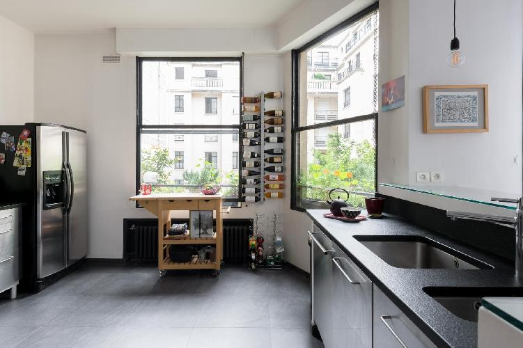 sleek kitchen with  sleek silver cabinets and windows framed the verdant courtyard in Paris luxury a