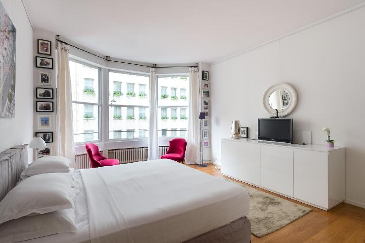 cozy master bedroom with a king-size bed and two plump pink armchairs in Paris luxury apartment