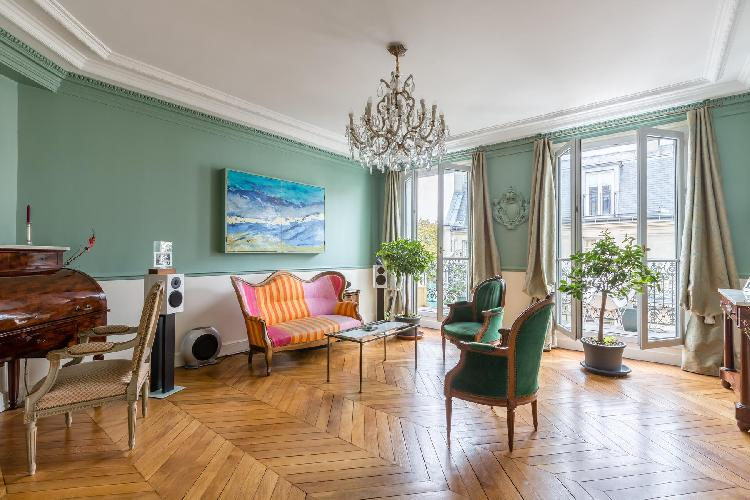 elegant living room with walls painted in Russian green with its tall windows dressed in the soft-co